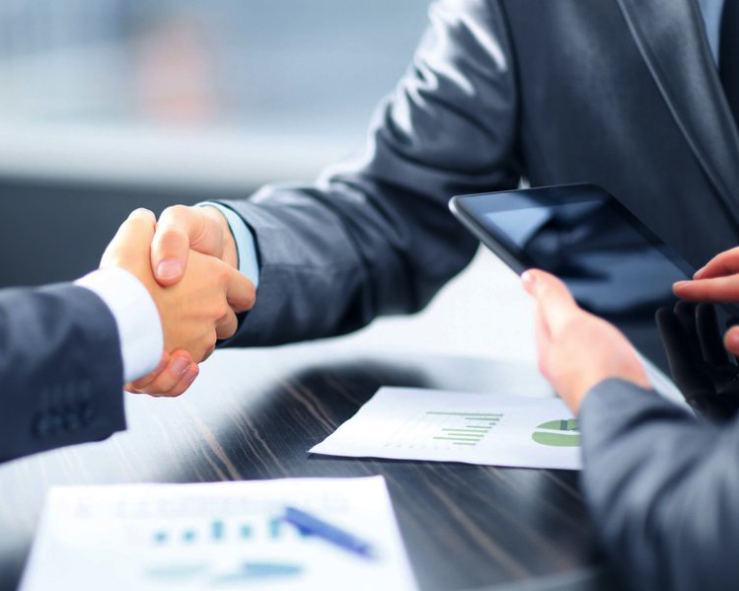 Image of three men meeting and shaking hands